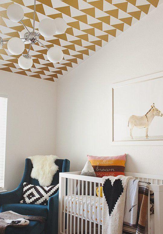 une chambre d'enfant confortable avec un plafond imprimé géométrique, des textiles imprimés lumineux, une chaise bleue et une œuvre d'art amusante