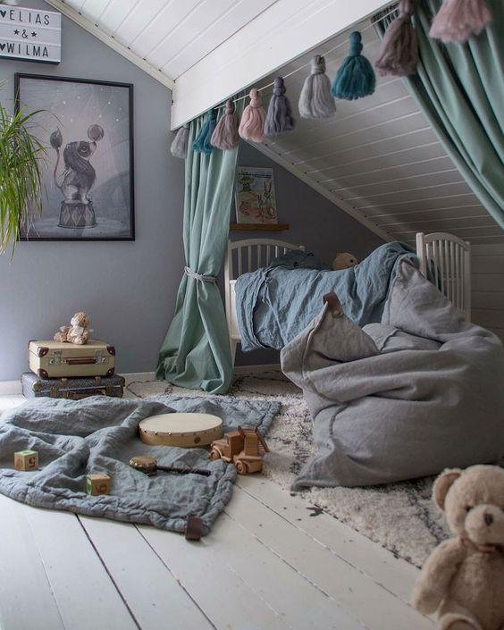une pépinière créative au grenier avec des textiles aux couleurs douces, des tapis superposés, une guirlande de pompons, des œuvres d'art et de nombreux jouets