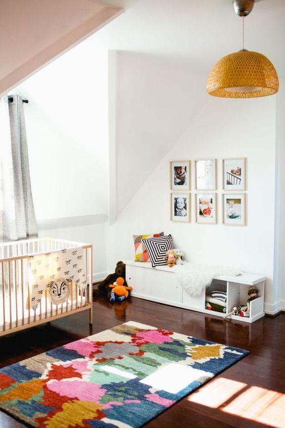 une chambre d'enfant mansardée colorée avec un plafond rose, un mur de galerie, des textiles imprimés aux couleurs vives et une suspension en osier