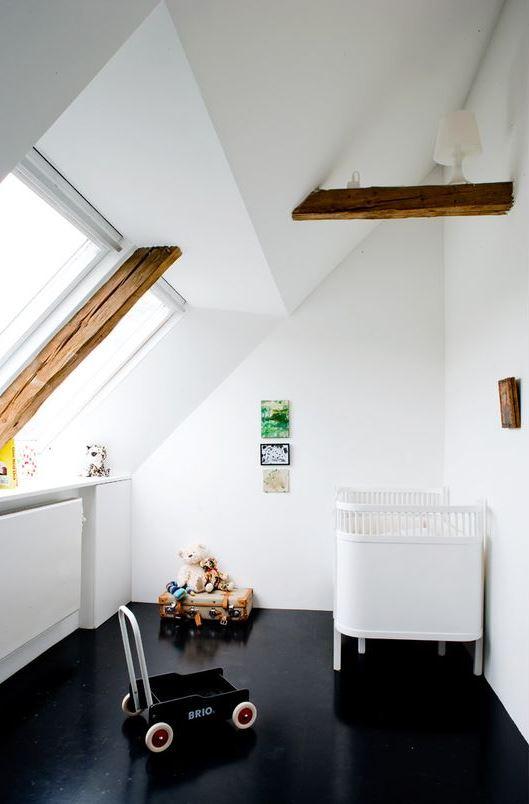 une pépinière mansardée contrastante avec un sol noir, des poutres en bois, un berceau blanc, des jouets et un mur de cuisine lumineux