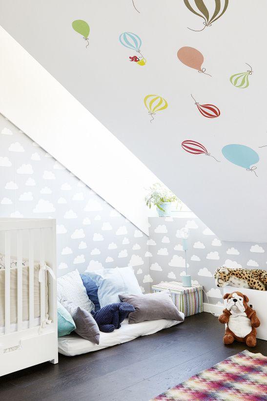 une pépinière mansardée amusante avec des oreillers colorés, un mur de montgolfière, un mur de nuages et des jouets audacieux