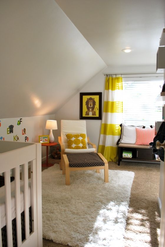 une chambre d'enfant mansardée neutre avec une chaise IKEA, un berceau, des touches jaunes et noires vives et des oreillers lumineux