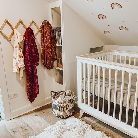 une pépinière amusante avec un mur imprimé arc-en-ciel, un petit berceau, des textiles aux couleurs vives et un meuble de rangement près du lit