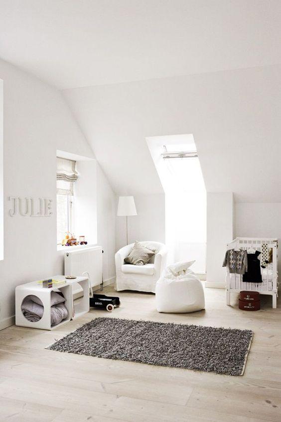 une chambre d'enfant moderne et neutre avec deux fenêtres, des meubles blancs, un tapis et de nombreux rangements pour un petit enfant