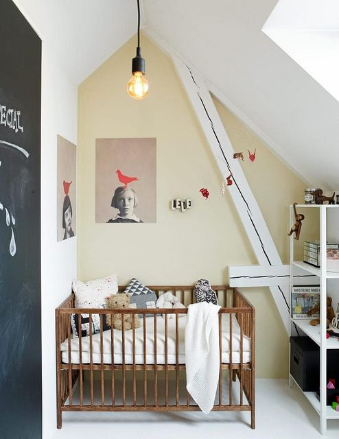 une petite pépinière mansardée avec une œuvre d'art accrocheuse, une porte de tableau, un simple berceau et un meuble de rangement pour un look moderne