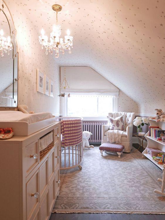 une petite chambre d'enfant mansardée d'inspiration vintage avec un lustre en cristal, une grande commode, quelques meubles pour les enfants et les adultes