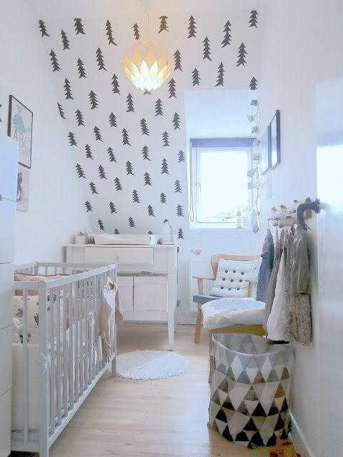 une pépinière nordique avec un mur de sapin, une boîte noire et blanche, des meubles neutres et quelques œuvres d'art pour une ambiance