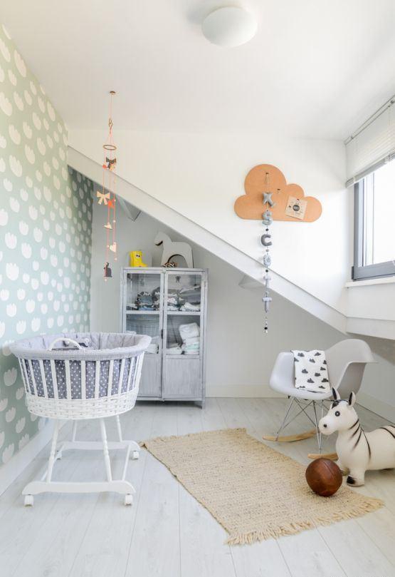 une chambre d'enfant fantaisie neutre avec des murs gris, un mur d'accent de nuage, des textiles imprimés, des mobiles et des guirlandes