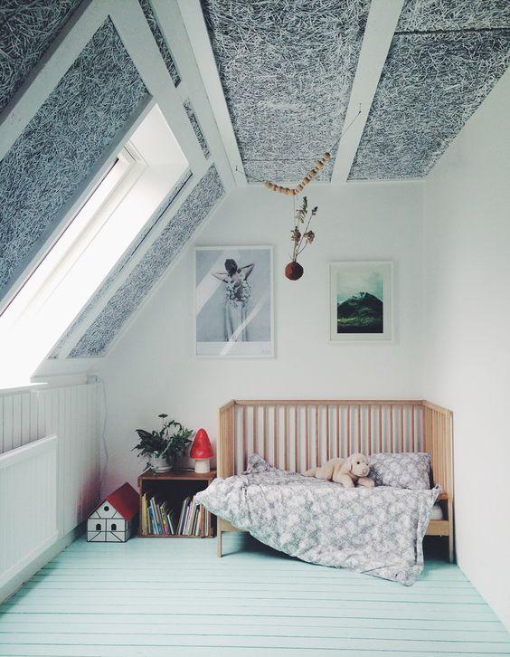 une pépinière mansardée avec un sol en menthe, un plafond lambrissé noir et blanc, un berceau et quelques jouets et meubles de rangement