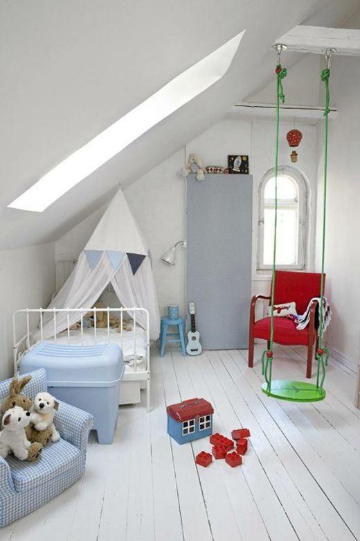 une pépinière mansardée blanche avec des meubles et des jouets colorés, avec une balançoire est très amusante et très accueillante