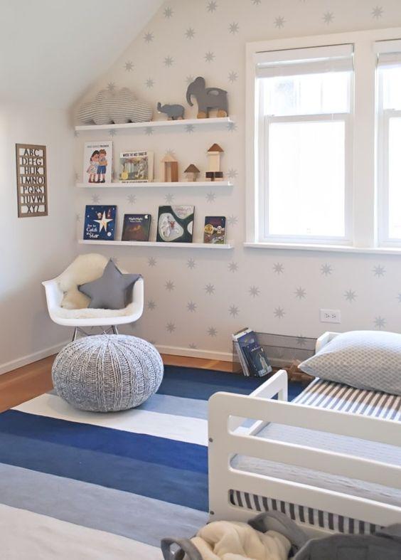 une pépinière étoilée avec un mur imprimé d'étoiles, des textiles bleus, une étagère ouverte et beaucoup de jouets et de livres