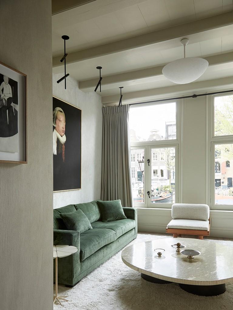 Le salon est plein de lumière, le mobilier est neutre et de couleur sourde, il y a des œuvres d'art