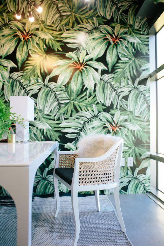 un bureau à la maison tropical audacieux avec un mur d'accent, des chaises en cuir, des touches d'or et de laiton et de verdure