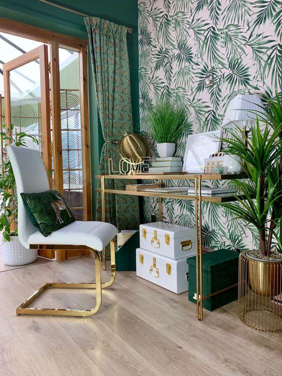 un bureau à domicile tropical lumineux et glamour avec un mur d'accent, des boîtes vertes et blanches, un bureau en verre doré, des jardinières en laiton et une chaise glamour