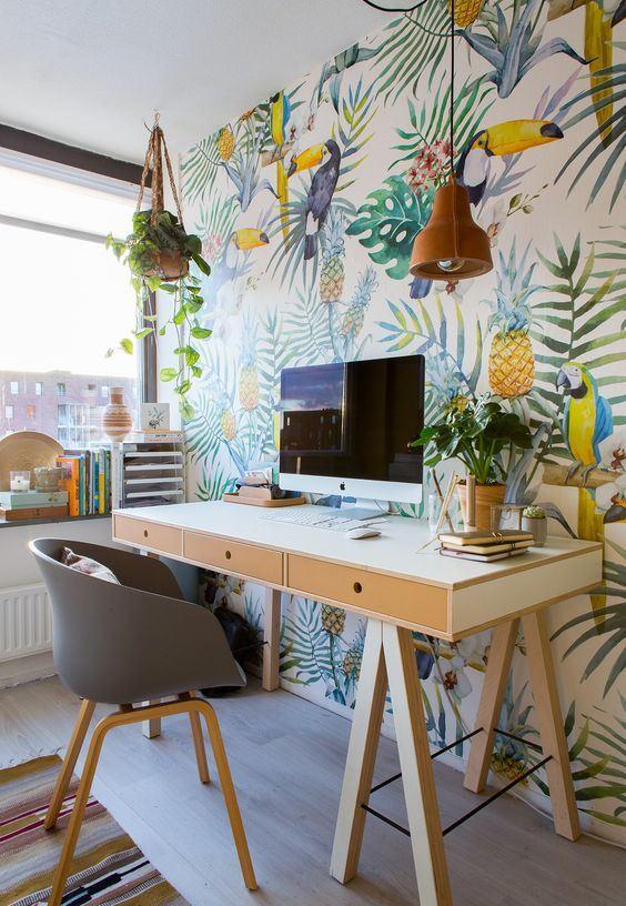 un bureau à la maison tropical lumineux avec un mur d'accent super audacieux, une lampe en liège, des plantes, un bureau à chevalet et une chaise grise