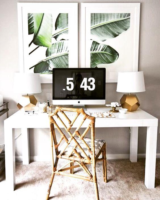 un coin de bureau tropical chic avec une chaise en rotin, des lampes de table dorées, des œuvres d'art tropicales et un bureau blanc