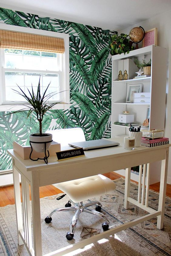 un bureau à domicile tropical cool et accueillant avec un mur de feuilles tropicales, des nuances tissées, des plantes tropicales et des touches de rose
