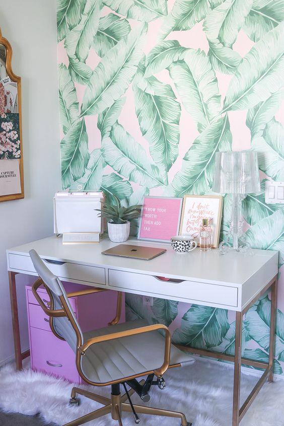un coin de bureau tropical lumineux avec un mur de feuilles tropicales, une unité de rangement rose et de l'art et des touches d'or et de laiton