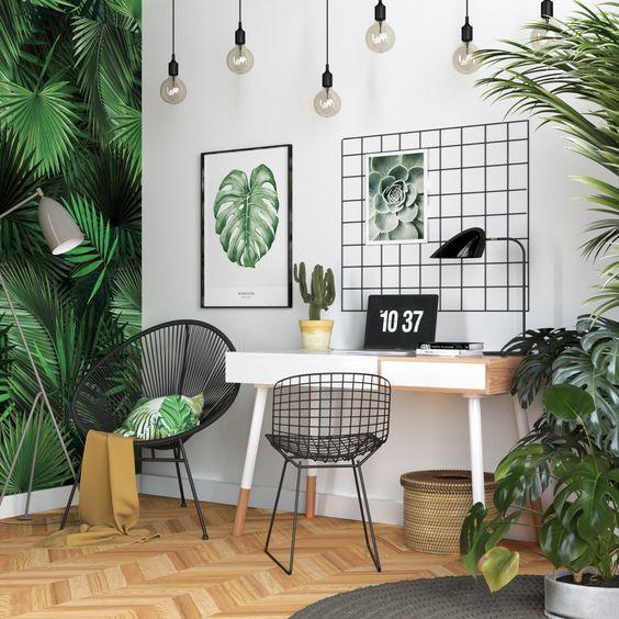 un bureau à la maison tropical lumineux avec un mur de feuilles tropicales, beaucoup de verdure en pot, des œuvres d'art, un panier tressé et des ampoules suspendues