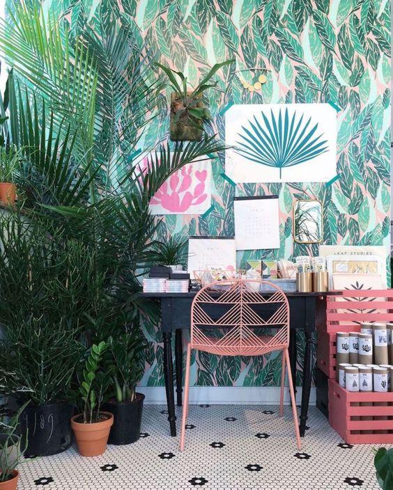 un bureau à la maison tropical lumineux avec du papier peint tropical, des œuvres d'art lumineuses et des plantes en pot, un bureau vintage et des meubles roses