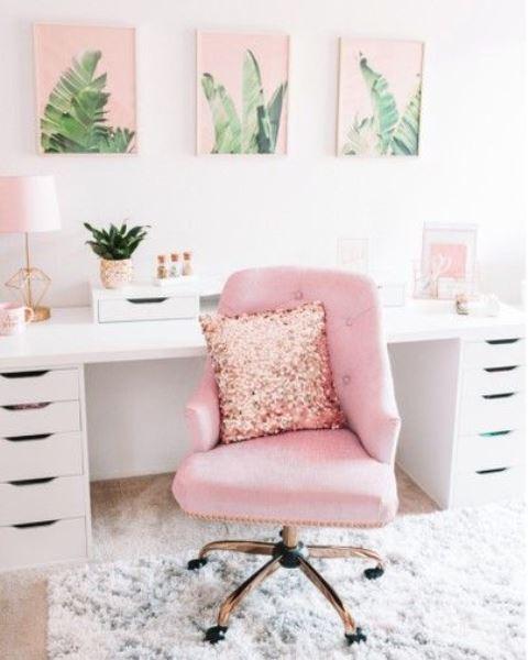 un bureau à la maison glamour avec des œuvres d'art tropicales roses, une chaise rose avec un oreiller à paillettes et d'autres touches de rose