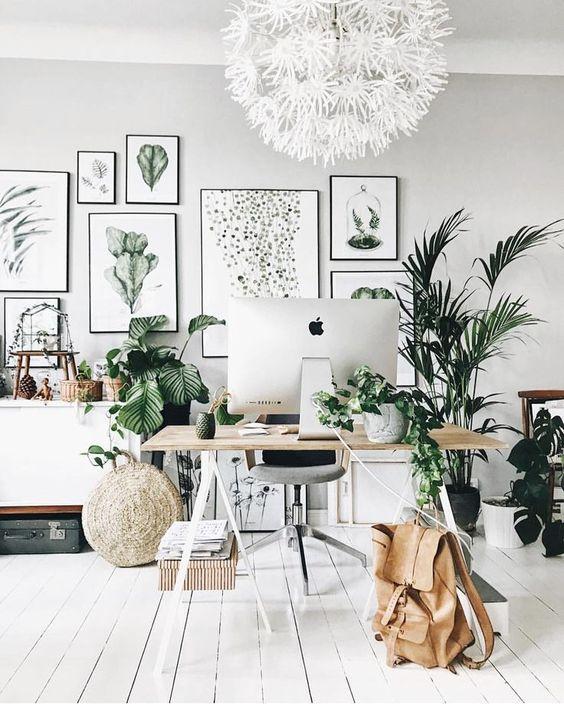 un bureau à domicile tropical neutre avec un grand mur de galerie, un lustre floral blanc, beaucoup de plantes, un bureau à chevalet et des paniers