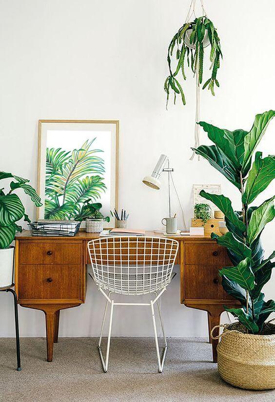 un bureau à domicile moderne du milieu du siècle dans des tons neutres, avec un desj en bois vintage, des plantes en pot et une œuvre d'art tropicale