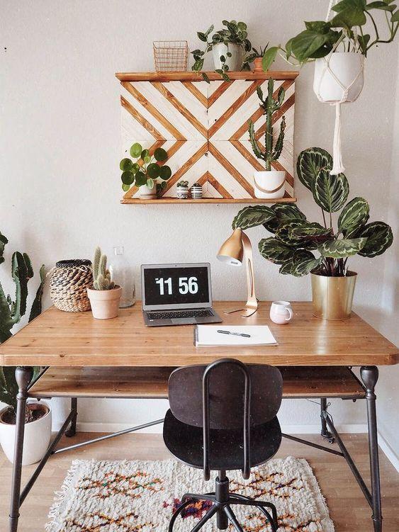 un bureau à domicile tropical moderne du milieu du siècle avec un bureau en bois et une chaise en métal vintage, des plantes en pot et des cactus ainsi qu'une œuvre d'art en chevron