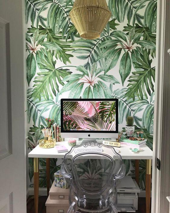 un petit bureau à la maison tropical avec un mur d'accent tropical, une lampe en rotin, une chaise pure, des touches d'or ici et là