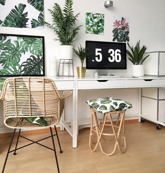 un bureau à domicile tropical dans des tons neutres, avec un mur de galerie tropical, des plantes en pot, une chaise et un tabouret en rotin et des touches d'or