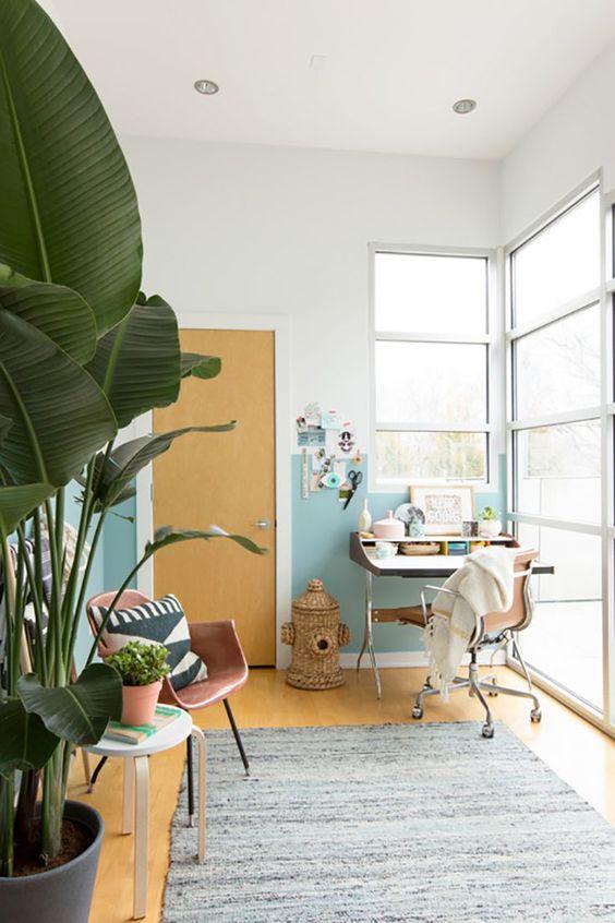 un bureau à domicile tropical fait avec du sable et des aquarelles, avec une poubelle tissée, des plantes tropicales et des chaises en cuir