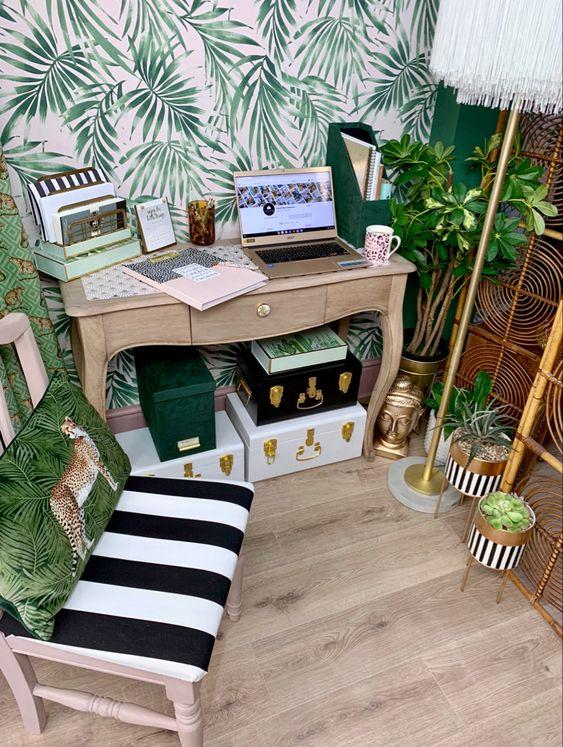 un petit bureau à domicile tropical avec un mur d'accent, un paravent en rotin, des jardinières en or, diverses boîtes, des oreillers tropicaux et des touches de laiton