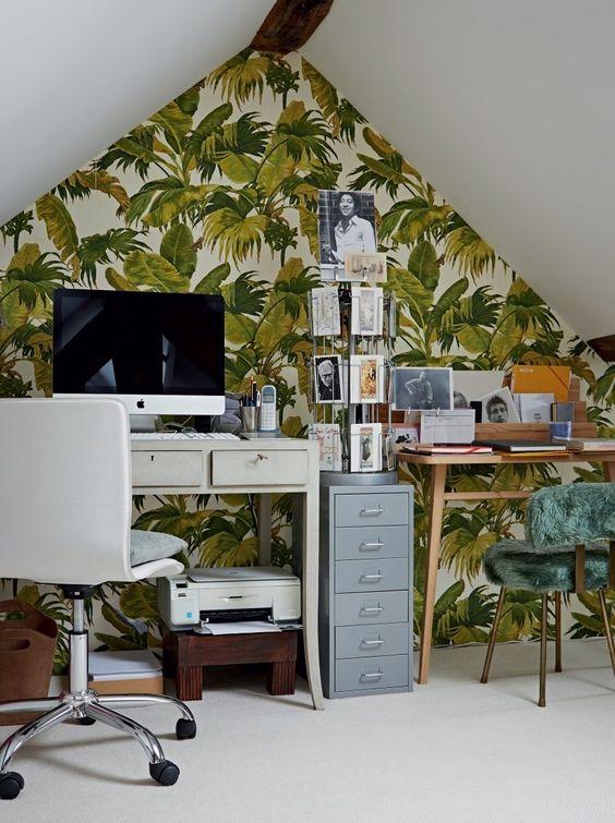un bureau à la maison tropical mansardé avec un mur d'accent, deux bureaux, une chaise en fourrure verte, un support avec des cartes et une chaise blanche
