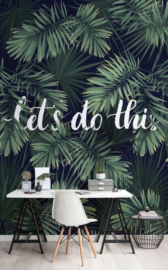 un bureau à domicile tropical avec une peinture murale au mur, un chevalet blanc, une table géométrique et une chaise blanche