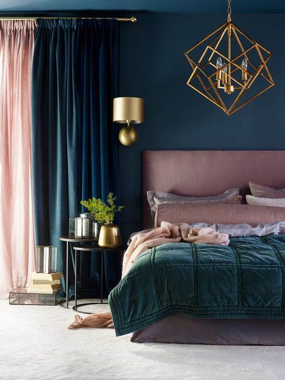 une belle chambre en bleu sarcelle et rose poussiéreux, avec un lit et une literie roses, un lustre doré et des appliques pour un look wow