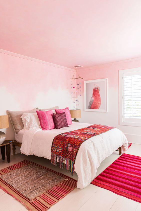 une chambre audacieuse avec des murs roses ombrés, un plafond rose, des oreillers rose vif, un tapis et une œuvre d'art de perroquet
