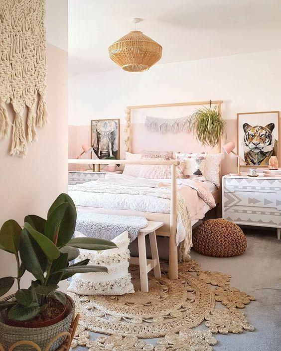 une chambre chic avec des murs roses, des oreillers roses et une couverture, des touches d'or et de laiton pour une sensation glamour