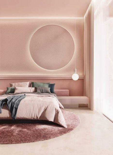 une chambre chic et moderne avec des murs roses et un plafond, avec un miroir rond éclairé, une ampoule, une literie de couleur sourde et un tapis rond rose