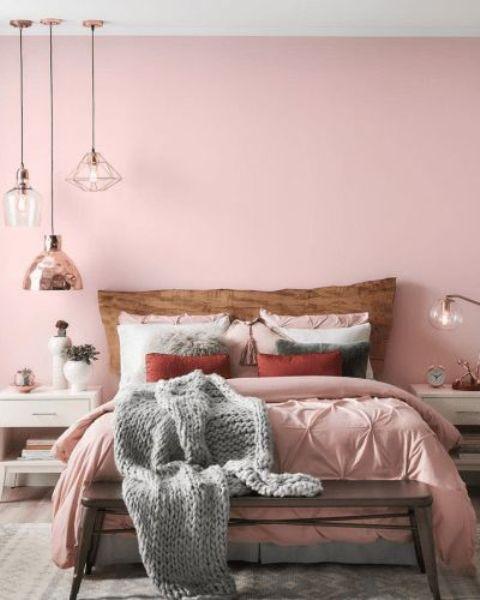 une chambre contemporaine chic avec un mur rose, une literie rose, des touches de gris, des suspensions et des meubles blancs