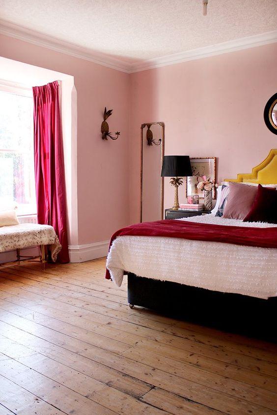 une chambre audacieuse et fantaisiste avec des murs roses, des rideaux fuchsia, des oreillers tendance, un lit noir et des lampes