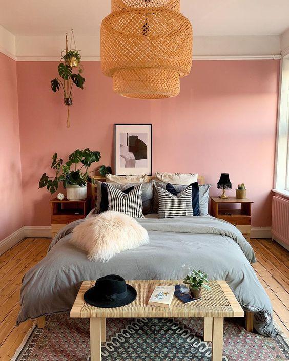 une chambre moderne et bohème avec des murs roses, des meubles en bois, une lampe en osier, de la verdure en pot et un oreiller en fourrure de faur