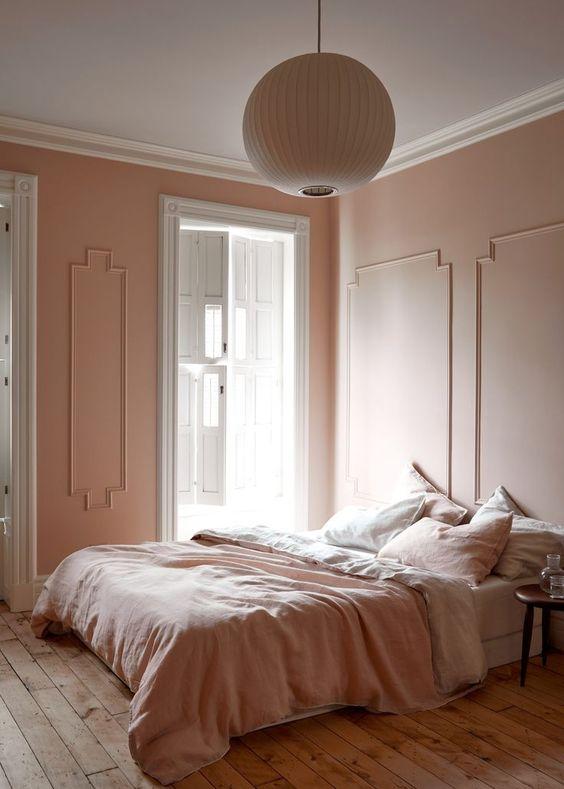une chambre à coucher raffinée d'inspiration vintage avec des murs à moulures blush, une literie blush et blanche, un plancher en bois et une lampe en papier