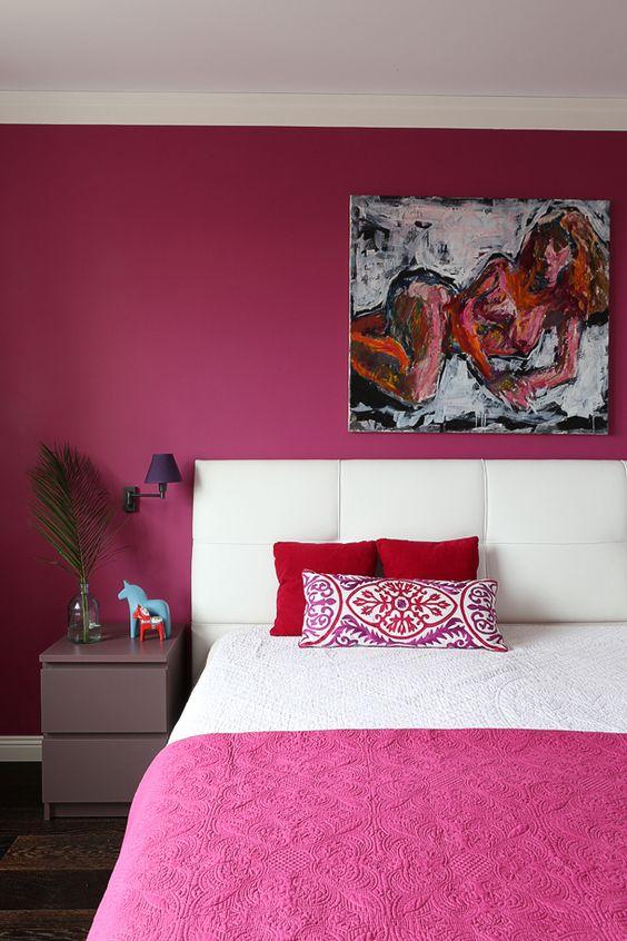 une chambre originale avec un mur et un couvre-lit fuchsia, une œuvre d'art, une table de chevet lavande et des appliques violettes