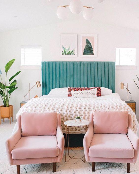 une chambre moderne et élégante dans des tons neutres agrémentée d'un lit vert, de chaises roses et d'un mur de galerie cool qui lie ces couleurs