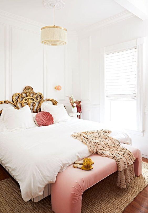une chambre raffinée dans des tons neutres, avec un lit exquis en or, un banc et un oreiller roses et un lustre à pampilles