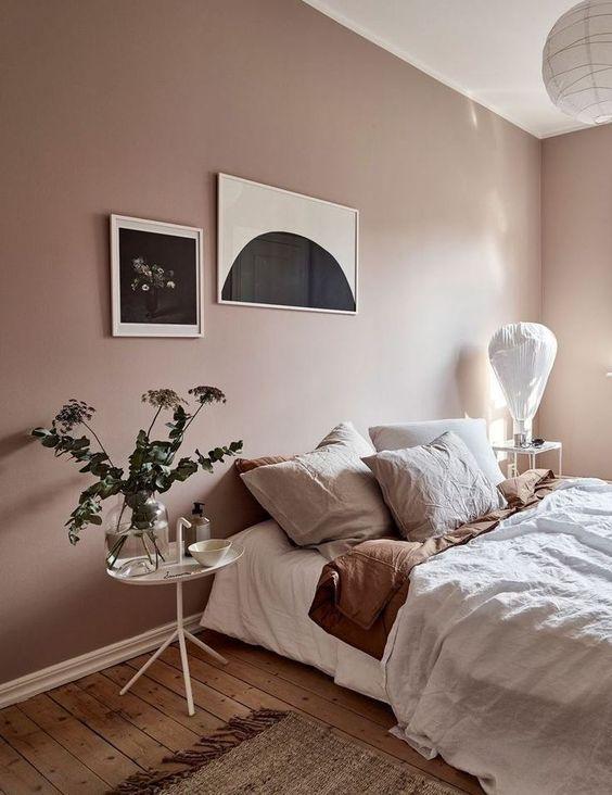 une chambre de rêve avec des murs blush, une literie de couleur sourde, de la verdure et un mur de galerie monochromatique