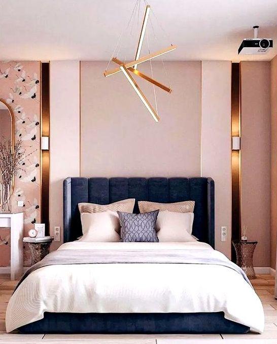 une chambre moderne et luxueuse avec des murs roses, du papier peint accrocheur, un lit bleu marine, une literie neutre et des touches d'or ici et là