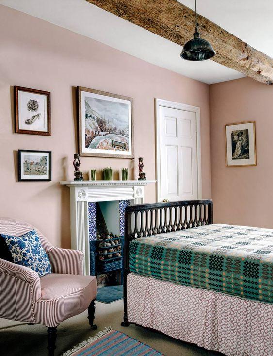 une chambre de ferme d'inspiration vintage avec des poutres en bois, des murs blush, une cheminée, des textiles imprimés verts et roses ici et là