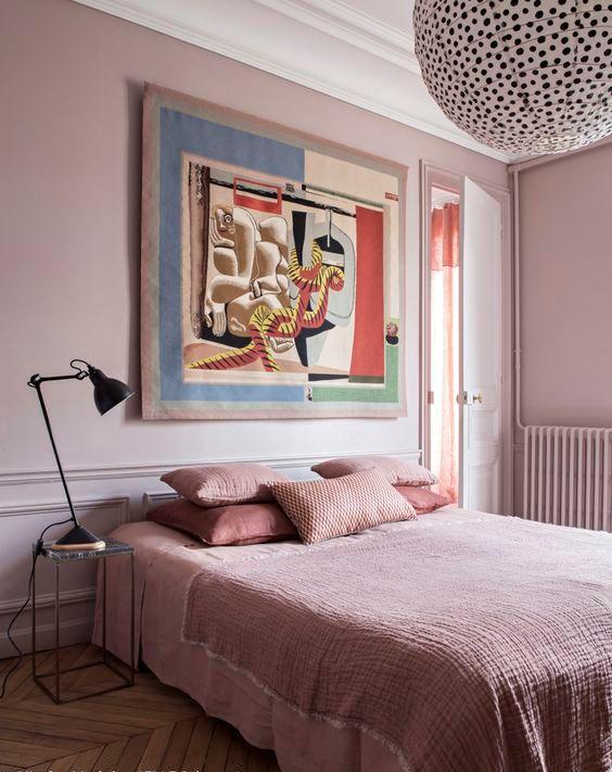 une chambre fantaisiste en rose clair, avec une literie rose clair et corail, une œuvre d'art unique, une lampe à pois et une table de chevet noire