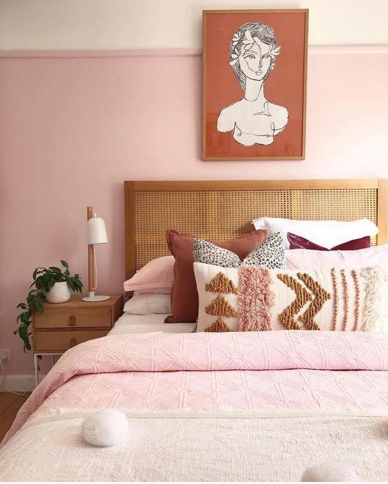 une chambre moderne et élégante avec des murs rose clair, une literie rose, neutre et bordeaux, des meubles en bois et une œuvre d'art remarquable